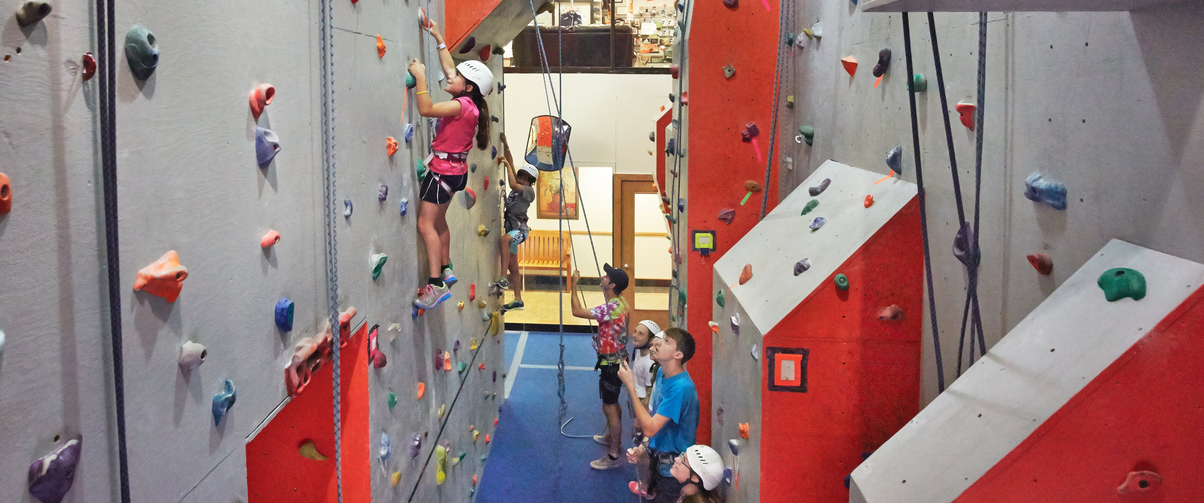 children on rock climbing wall with instructor