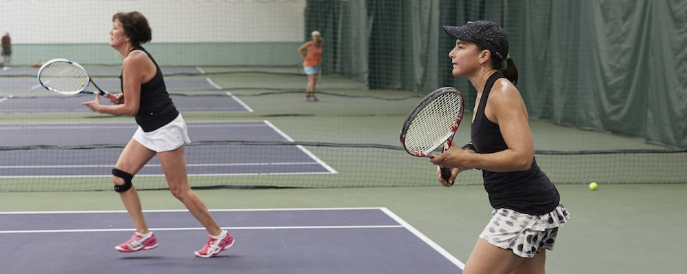 two women holding tennis racquets on tennis court